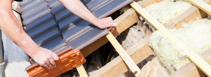 a roofer laying tiles on a roof